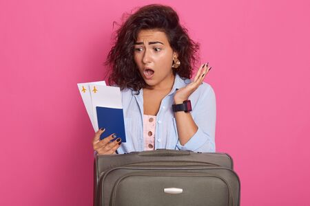 Young woman with dark curly hair wearing casual clothes keeping mouth opened, holding passport, boarding pass tickets, looking at her documents with shocking expression, isolated on rosy background. Banco de Imagens