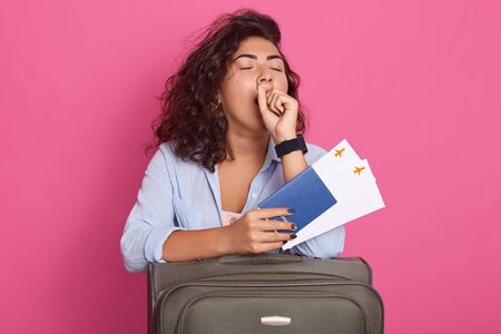 Beautiful modern yawning woman with suitcase, passport and air tickets in hands, wearing blue shirt, posing with closed eyes, waiting her plane, looks tired and sleepy, isolated over rose background. Фото со стока