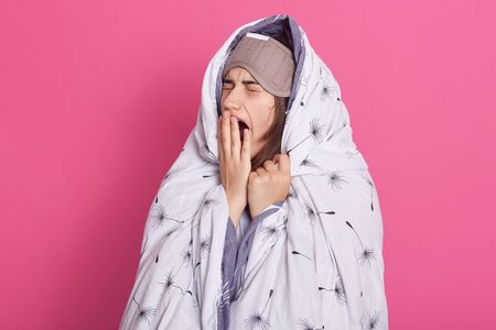 Portrait of relaxed young lady closing her eyes, opening mouth widely, yawning, having desire to sleep, covering her mouth with hand, standing under blanket, wearing sleeping mask. Rest concept.