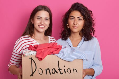 Close up portrait of two girls volunteering, women holding paper box with clothes for poor people, friends making donation, attractive female wearing stylish outfits posing against pink studio wall. 写真素材