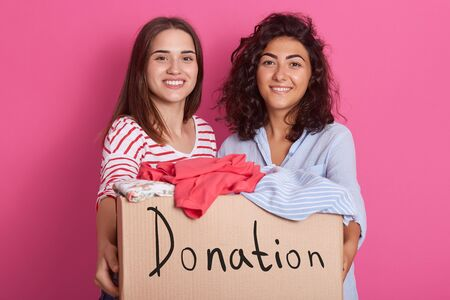 Image of two pretty brunette girls wearing red striped and blue shirts, presenting box with vivid clothes preparing for commission shop isolated on pink background. People and donation concept.