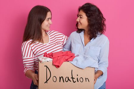 Close up portrait of two girls volunteering, women holding box with clothes for poor people, attractive female making donation, ladies posing and looking at each other. People and charity concept. 写真素材