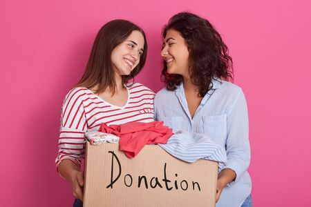 Close up of cheerful helpful volunteer girls standing isolated over pink background, holding box with different clothes. Full box of donated clothes. Smiling brunette women being happy to make charity Zdjęcie Seryjne