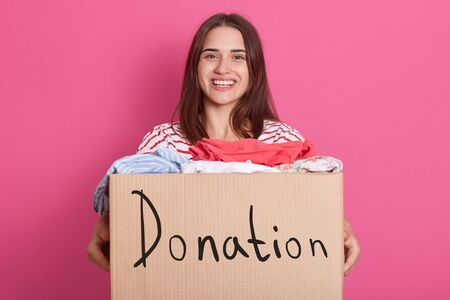 Cheerful helpful volunteer standing isolated over pink background in studio, holding box with inscription Donation, full of donated clothes. Smiling brunette woman being happy to do good things. Zdjęcie Seryjne