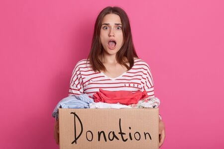 Image of shocked emotional lady with widely opened mouth and eyes, being surprised, having carton box with donated clothes in hands, looking directly at camera. People and volunteering concept.