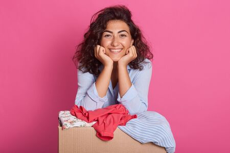 Portrait of cute attractive dark haired girl stands near cardboard box with clothes isolated on rosy background, keeps hands under chin and looks smiling directly at camera. Donation, charity concept. Фото со стока