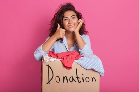 Portrait of happy young woman with clothes donation standing over rosy background, wearing casual outfit, keeps one hand under chin and making ok sign with other hand. Donation, charity concept.