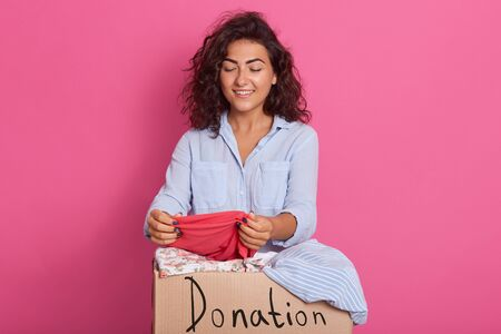 Close up portrait of young woman with dark wavy hair, posing near clothes donation box, standing over pink background, holding red outfit in hands and looking down on it. Charity and people concept.