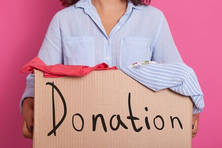 Image of faceless woman wearing blue casual shirt, holding box full of clothes for poor people, box with inspiration danation, charity for poor people, clothes for childrens home. Donation concept.