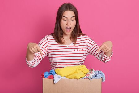 Picture of enthusiastic positive volunteer making gestures, pointing to carton box with forefingers, opening her mouth widely, wearing stripped sweatshirt, looking at various items of clothes.