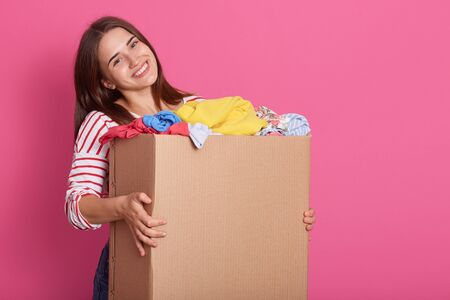 Portrait of cheerful tender female holding carton box in arms, taking items of clothes, being volunteer, having kind heart, smiling sincerely, looking directly at camera. Copyspace for advertisement.