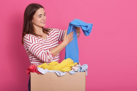 Image of brunette attractive lady looking aside, smiling sincerely, putting donated clothes in order, holding blue trousers in hands, wearing stripped sweatshirt. People and donation concept.