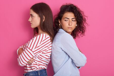 Profile portrait of beautiful girls with dark hair frowning her face in displeasure, wearing casual shirts, keeping arms folded, do not talk to each other, posing isolated over pink studio background.