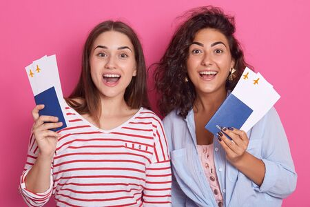 Two happy brunette girls in colorful clothes holding passport, boarding pass ticketnisolated on rose background, having surprised facial expressions. People, lifestyle and traveling concept. Banco de Imagens