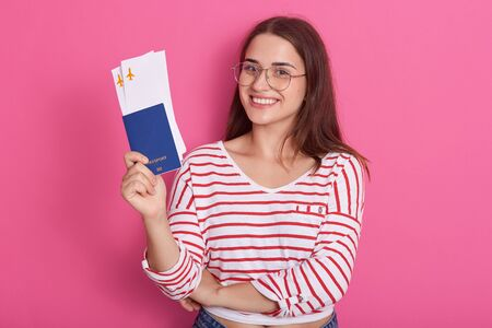 Smiling pretty young woman in white casual cshirt with red stripes holding passport, boarding pass tickets, happy passenger ready for boarding, isolated on pink. People lifestyle and tarveling concept