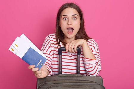 Excited young woman in white shirt with red stripes keeping mouth open, expresses astonish, holds pass port and boarding pass tickets isolated on rose background. People, lifestyle and travel concept. Banco de Imagens