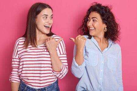 Indoor shot of two young beautiful girls pointing towards each other, brunette women dress shirts, standing against pink studio background, expresses happynes and astonish. Same sex love concept. Фото со стока