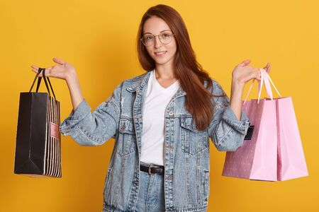 Photo of attractive happy stylish woman shopaholic holding shopping bags over yellow studio background, wearing denim jacket, jeans and white t shirt. People, shopping and lifestyle concept.