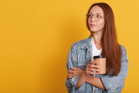 Close up portrait of pensive woman with dark hair, looking aside, contemplates about something, wearing white t shirt, denim jacket abd eyewear, holding disposable cup of coffee, over yellow wall.