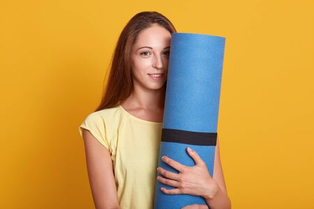 Indoor shot of young beautiful woman athlete wearing t shirt stands holding blue fitness mat and looking at camera with dreaming of future sport achievement. Sport, lifestyle and fitness concept.