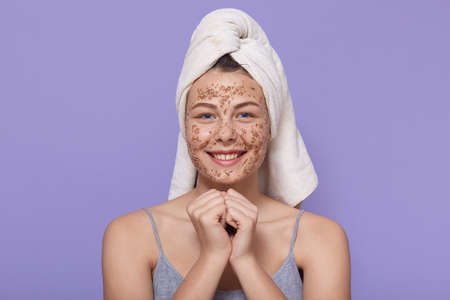 Spa teen girl applying facial clay mask, wearing white towel over head, looking smiling directly at camera, keeping fists under chin, lady doing cosmetic procedures, beauty treatments.