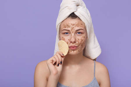 Attractive woman holds soft little sponge for facial treatments, stands wrapped in white towel, applies fresh clay mask for cleaning face, doing procedures for healthy skin Archivio Fotografico - 151764152