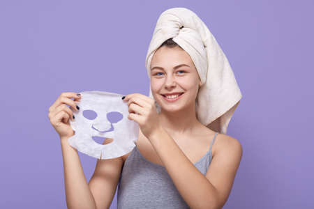 Pretty young female holds beauty mask in hands, being ready to apply it on face for rejuvenating, lady wears white towel on head, poses over lilac background. Archivio Fotografico - 151764173