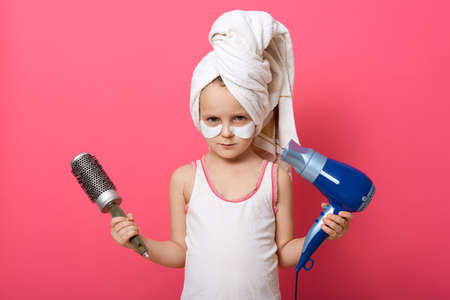 Cute little girl posing with round brush dryer and hairdryer in hands, serious little cute female with patches under eyes and white towel on head, offended kid doing morning procedures.