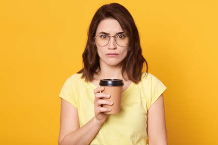 Serious dark haired woman holding cup of coffee, wears casual t shirt and eyewears, has sad expression, isolated over yellow background, lady being in bad mood. Stockfoto