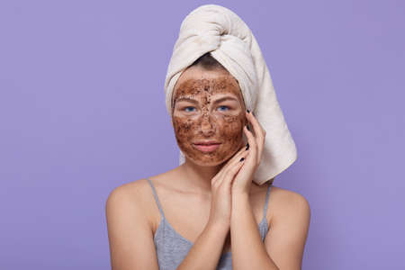 Beautiful young female with chocolate mask on face, poses with white towel on head, having spa procedures at home, isolated over lilac wall, doing renewing manipulation for her skin.