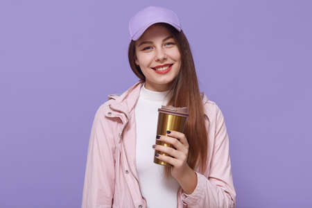 Shot of glad female student has coffee break after lectures, enjoys hot beverage from thermo mug, posing isolated over lilac background, wearing casual attire. Archivio Fotografico - 151764180
