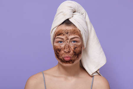 portrait of young attractive woman with white towel on her head, posing isolated over lilac background with pouty lips, looks directly at camera, having chocolate scrub or mask for moisturizing. Archivio Fotografico - 151764182