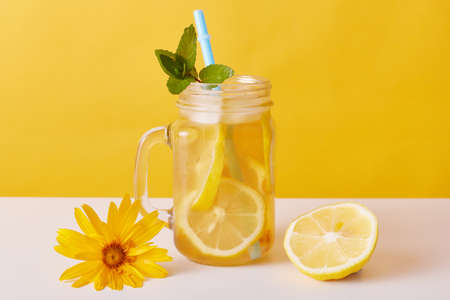 Iced tea with lemon slices and mint, glass pitcher with citrous refreshing summer cocktail and drinking straw on table decorated with flower and half of lemon. Archivio Fotografico - 151850897