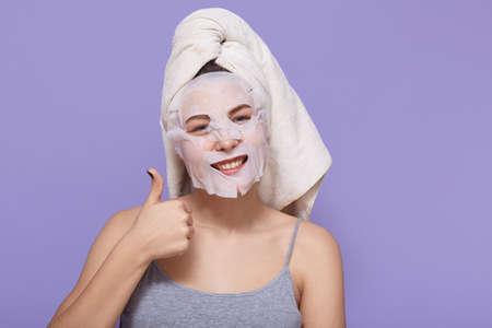 Positive young woman shows her big thumb up while posing with cosmetic mask on her face. Woman has white towel around her hair and sleeveless t shirt, standing isolated over lilac background. Archivio Fotografico - 151764183