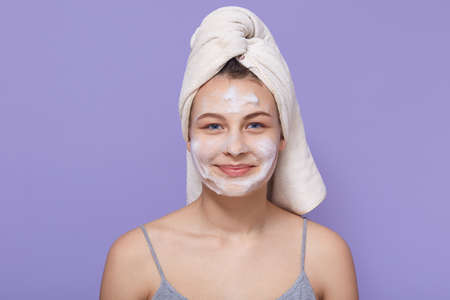 Woman with pleasant appearance, being wrapped in white towel and white facial mask on face, female posing with charming smile against lilac background. Archivio Fotografico - 151764185