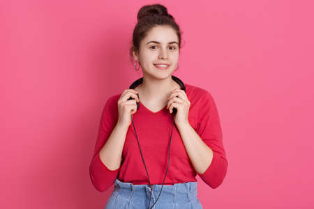 Closeup portrait of good looking cute charming attractive teen girl wearing red shirt, female with knot listening to pop music isolated over pink background. Archivio Fotografico - 151764189