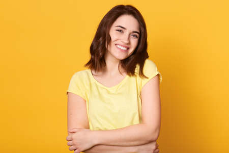 Yourself style stylish person optimClose up portrait of cute lovely charming adorable girl hugging herself isolated over yellow background, looking smiling at camera. Archivio Fotografico - 151764191