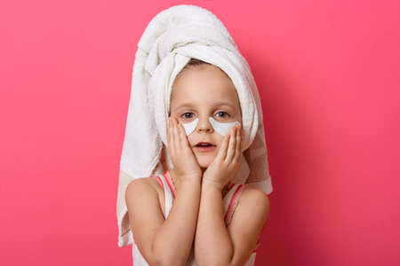 Little cute girl wearing white towel on head, posing with patches under eyes, standing against pink background, charming female kid repeats after mother doing morning procedures.