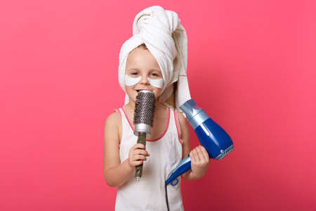 Cute female child imagines she super star and singing with comb in hands, charming little girl with patches under eyes and towel against rosy wall, holding hairdryer in other hand. Archivio Fotografico - 151764208
