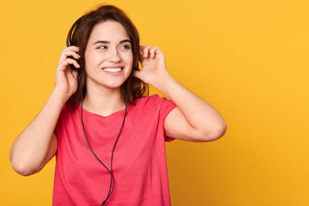 Portrait of beautiful young woman keeping hands on headphones, looks happy, looking aside, wearing red casual t shirt, posing isolated over background. Archivio Fotografico