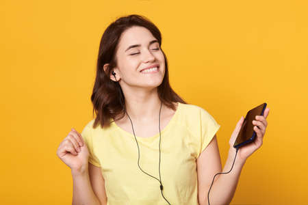 Gorgeous female with satisfied facial expression, toothy smile and closed eyes listening to music while posing isolated over yellow background, lady wearing casual t shirt. Archivio Fotografico - 151764214