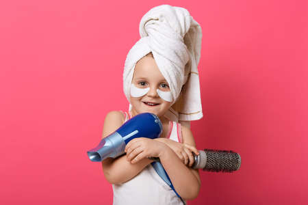 Portrait of beautiful little smiling girl with hair dryer and brush in hands, posing with white towel on head against pink wall, having patches under eyes. Archivio Fotografico - 151764216