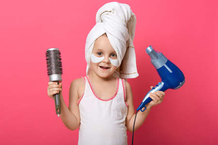 Adorable female child holding hair dryer and comb in hands, looking at camera while having morning procedures, posing with towel on her head and with patches under eyes.