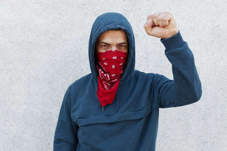 Stop racism. Photo of protester with red bandana mask raises fist, activist of community against afro citizens lawlessness, guy posing isolated over white background. Archivio Fotografico - 151764219