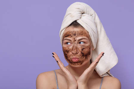 Attractive lady making funny face while doing peeling procedures for face at home, keeping palms near cheeks, looking aside, has white towel on head, keeps lips rounded. Archivio Fotografico