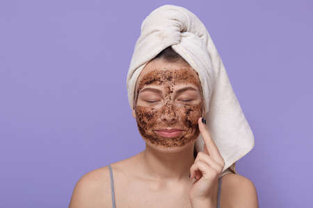 Portrait of young female applies homemade facial clay mask, has white towel wrapped around head, keeping eyes closed, stands with finger on cheek against lilac background. Beauty treatment at home.