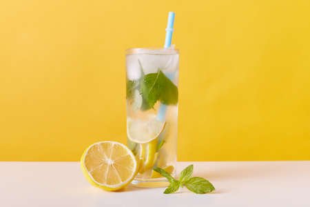 Homemade refreshing summer lemonade drink with lemon slices, mint and ice cubes, glasses with drinking straw isolated over yellow wall, detox cocktail.