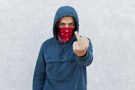 Close up photo of young guy in bandana mask calls for stopping police brutality, showing symbol, fight for equal rights and against racism isolated over white background.