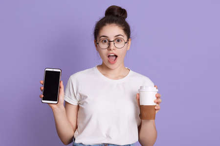 Portrait of shocked surprised woman with dark hair and knot, holding take away coffee cup and mobile phone while standing isolated over lilac background. Archivio Fotografico - 151764263