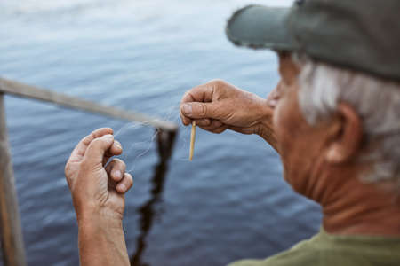 Senior man with gray hair wearing baseball cap and green t shirt baits fishing rod, elderly male spending time near river or lake, having rest in open air. Archivio Fotografico - 151764264